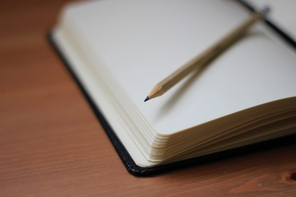 Photo of a blank paged notebook and pencil, by Jan Kahánek on Unsplash