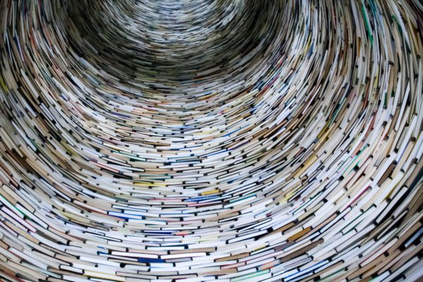A round circle made up of books, looking like a tunnel. Photo by _HealthyMond . on Unsplash