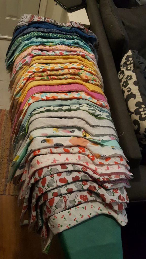 25 plus wine bags in partial construction laid side by side on an ironing board