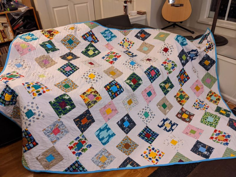 Finished animal themed patchwork quilt laid across the couch