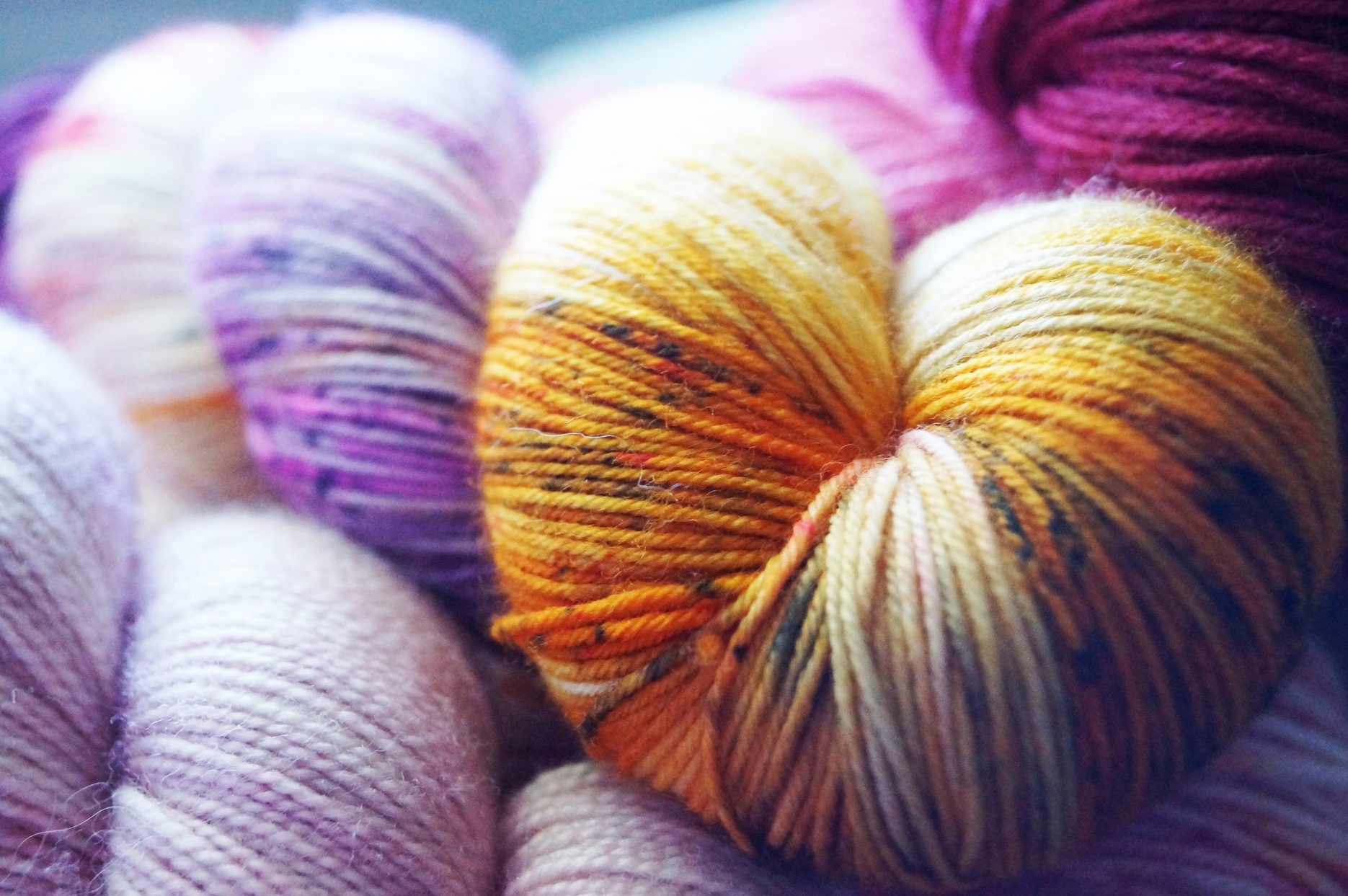 Several colorful skeins of yarn. Photo by Hannah Cole on Unsplash